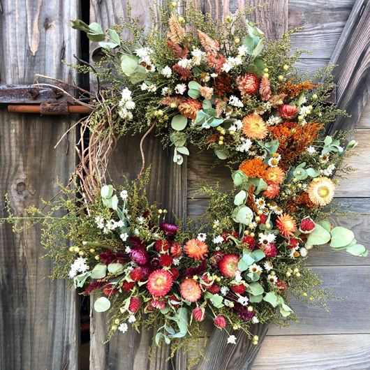 A rustic, winter wreath featuring an array of dried flowers and foliage.