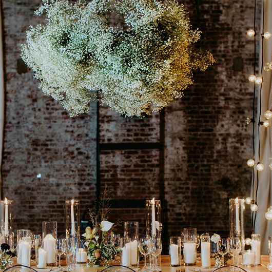 A dramatic chandelier of Gypsophila stems adds an airy feel to this elegant tablescape.
