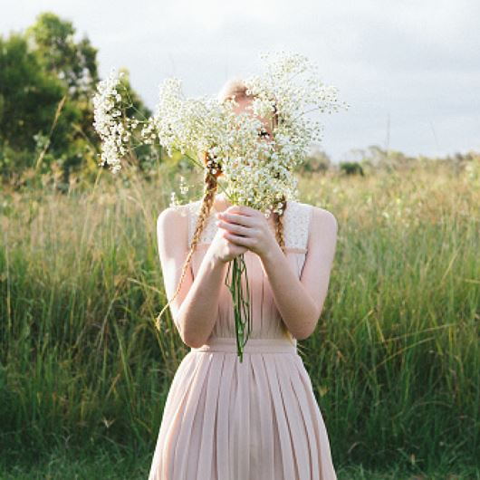 Girl in meadow holding Gypsophila ​stems.
