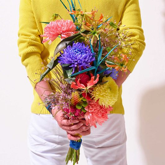 A festive, hand-tied bouquet showcasing brightly-colored Chrysanthemums.
