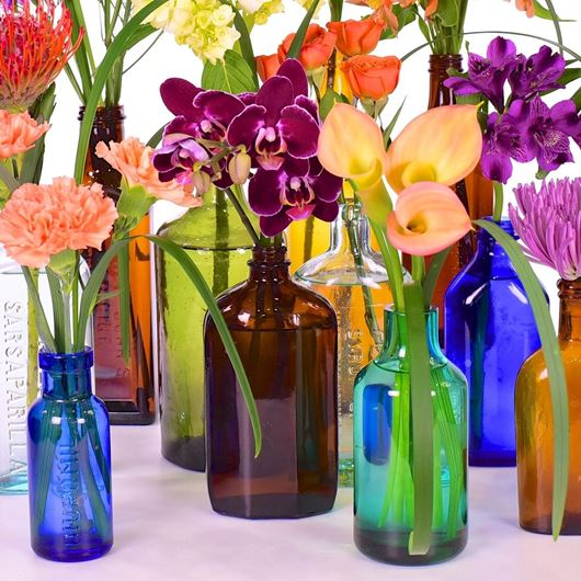 A collection of antique bottles with callas, orchids, carnations, Alstroemerias, and chrysanthemums.  Photo: Jason Edwards